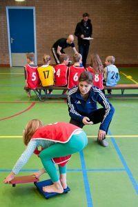 een meisje staat in een gymzaal gebukt op een blauw plankje en legt een bruin plankje erbij. Een begeleider kijkt toe