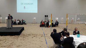 opening Voorzet door minister in een sportzaal waar zand op de grond ligt en deelnemers aan tafels zitten op het zand