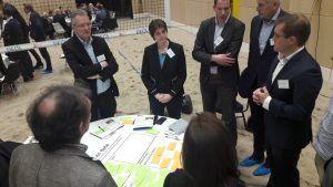 Deelnemers aan de conferentie zijn staand aan het overleggen rondom een tafel die in het zand staat