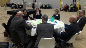 tafels in het zand in een sporthal waar de deelnemers aan de conferentie met elkaar in gesprek zijn