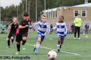 een scheidsrechter kijkt naar kinderen van 2 teams die tijdens een voetbalwedstrijd naar een bal rennen