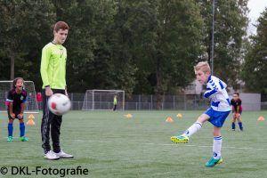 Een jonge scheidsrechter kijkt toe hoe ene jongetje de bal naar het doel schiet