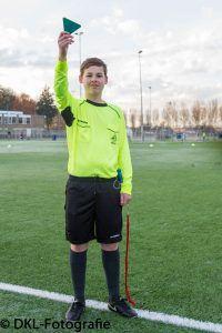 Een jonge scheidsrechter aan de kant van een voetbalveld