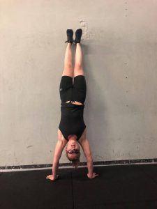 een vrouw in sportkleding doet een handstand tegen de muur