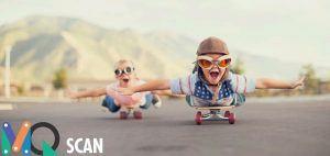 2 kindjes met grappige helm en bril liggend op een skateboard