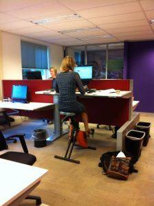 Medewerkster achter een bureau op een bureaufiets