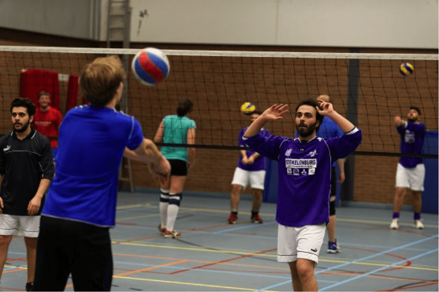 vluchtelingen die samen met autochtone bevolking volleybal spelen