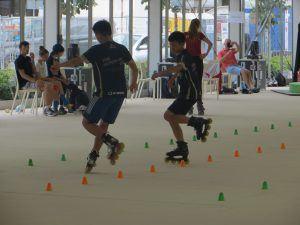 2 jongens op skates doen een behendigheidsoefening tussen kleine pionnetjes