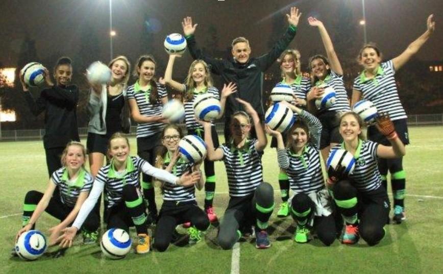 Teamfoto van de meiden van HC Delfshaven met Feyenoorder Jens Toornstra in hun midden.