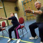 Ouderen doen een zittend op een stoel een oefening in een gymzaal