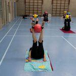 Mensen in een gymzaal die een oefening doen liggend op hun rug met de benen in de lucht en een bal tussen de enkels