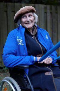 een oudere vrouw in een rolstoel trekt een sportelastiek naar zich toe
