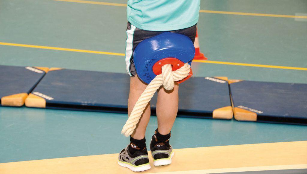 het touw in de gymzaal is omgetoverd als een schommel; kind klemt dit tussen zijn benen en staat op het punt zich af te zetten voor een zwaai naar de andere kant