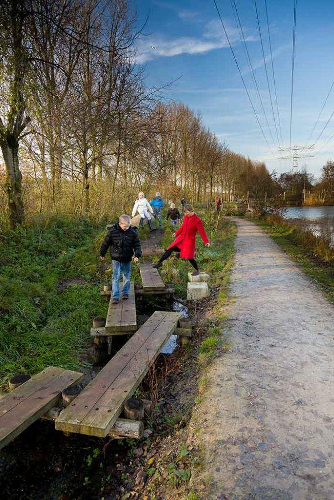 Ouder en kinderen lopen in een park van plank naar plank
