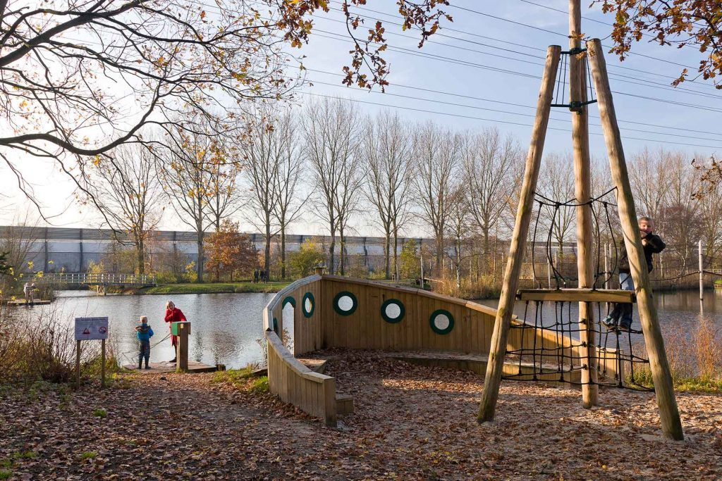 op een speelse manier is de waterkant ingericht dat uitnodigt om gaan spelen: van hout is een voorsteven van een boot gebouwd en de klimpaal dient als mast.