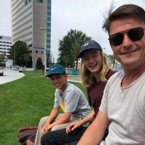 een man en twee kinderen vrolijk kijken in de camera in het skatepark