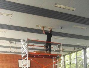 man werkt aan plafond in een gymlokaal