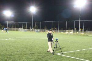 man met een fotostatief op een sportveld