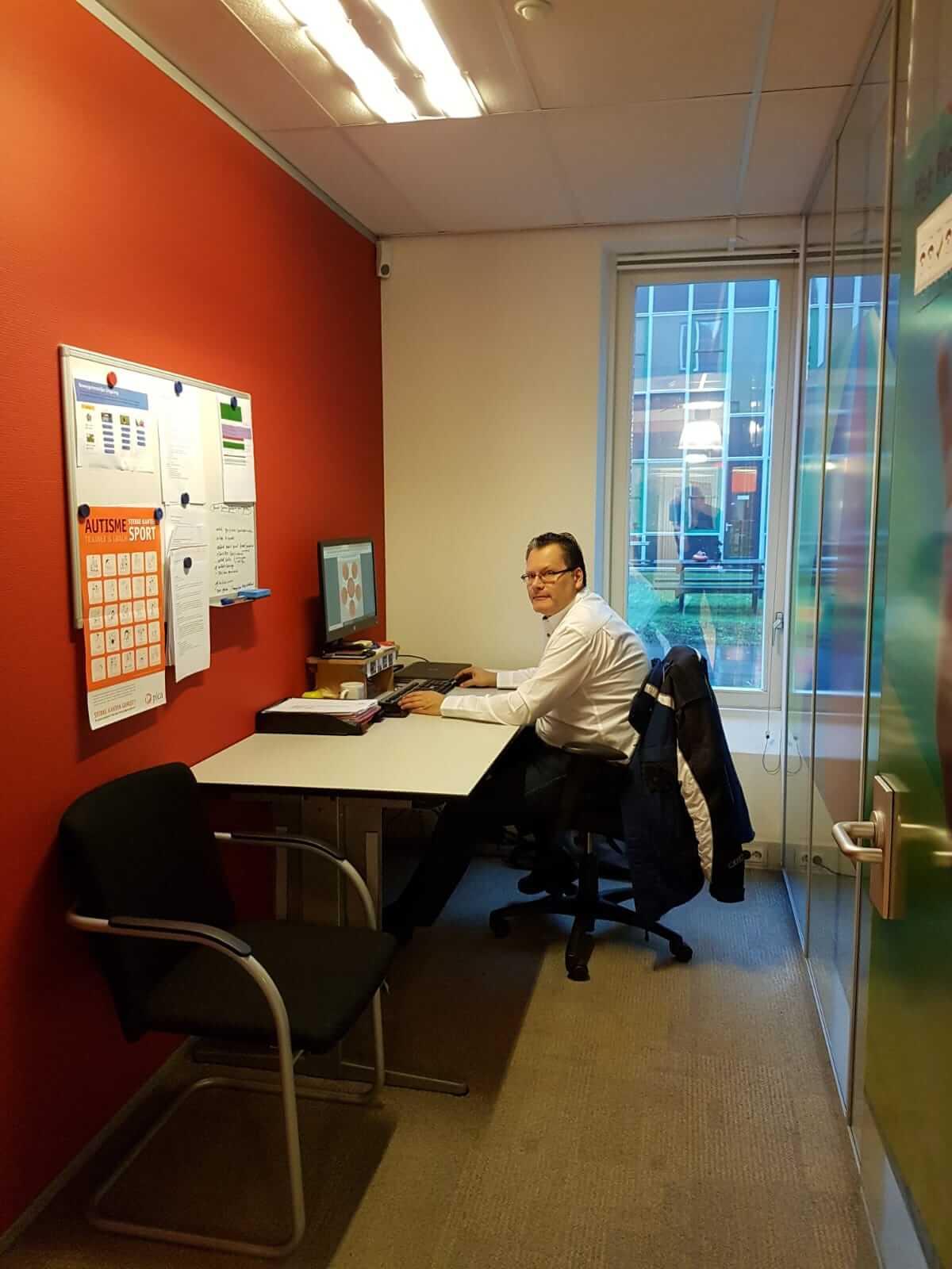 man achter zijn bureau op kantoor