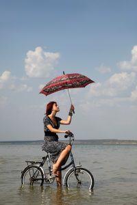 vrouw met paraplu op de fiets in de regen