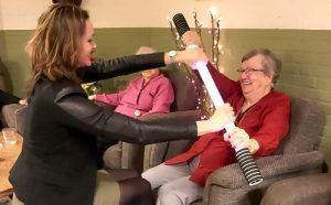 oudere dame, zit op een stoel en houdt een beweegstok in haar handen