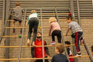 kinderen klimmen op een klimwand in de Gymzaal