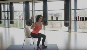 vrouw op een stoel in een fitnessruimte oefeningen aan het doen