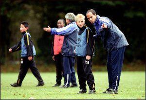 man legt iets uit met hulp van handgebaar aan een kind op de voetbalveld