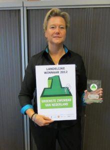 vrouw poseert voor de kamera met een certificaat en prijs in haar handen