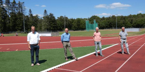 vier mannen poseren voor de camera op een atletiek vereniging