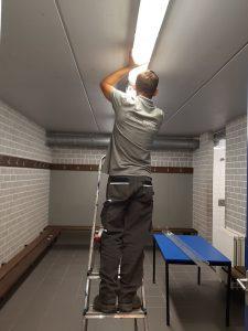 man instaleert LED verlichting in kleedkamer