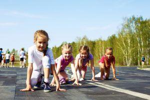 kinderen starten op een atletiekbaan