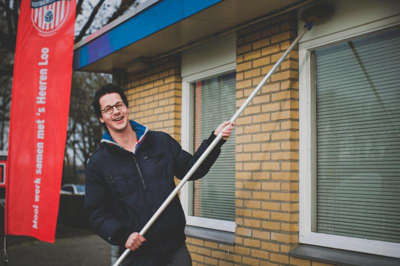 Jongeman poetst vrolijk de kozijnen van een raam