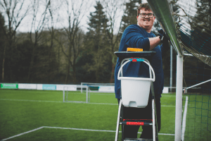 jongeman ramen aan het lappen op een voetbalvereniging