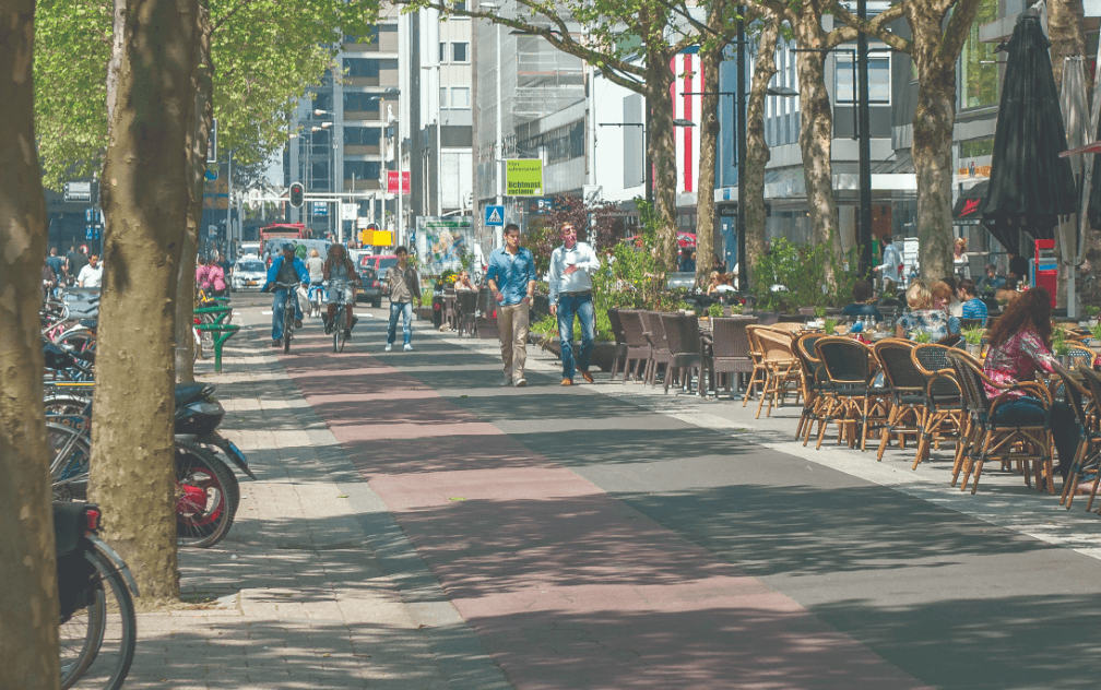 een straat in Rotterdam met terras, fietspad en loopstraat