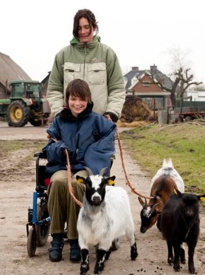 Jongere in rolstoel wordt geduwd door begeleider en er lopen geitjes mee