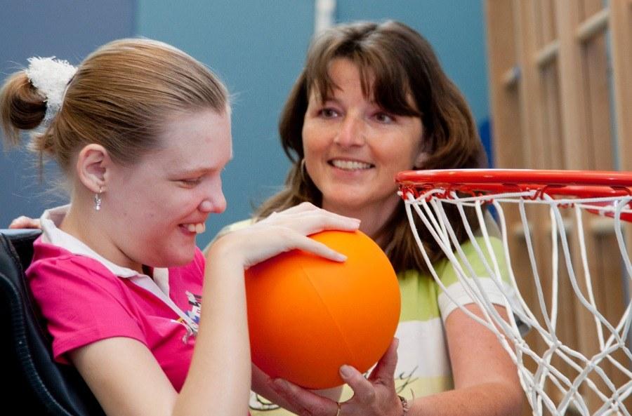 Meisje met een beperking wordt geholpen om een bal in een basketbalnetje te doen